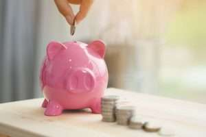 Pink pig piggy bank/savings pot with coins in piles to the right and a hand putting a coin in to the pot