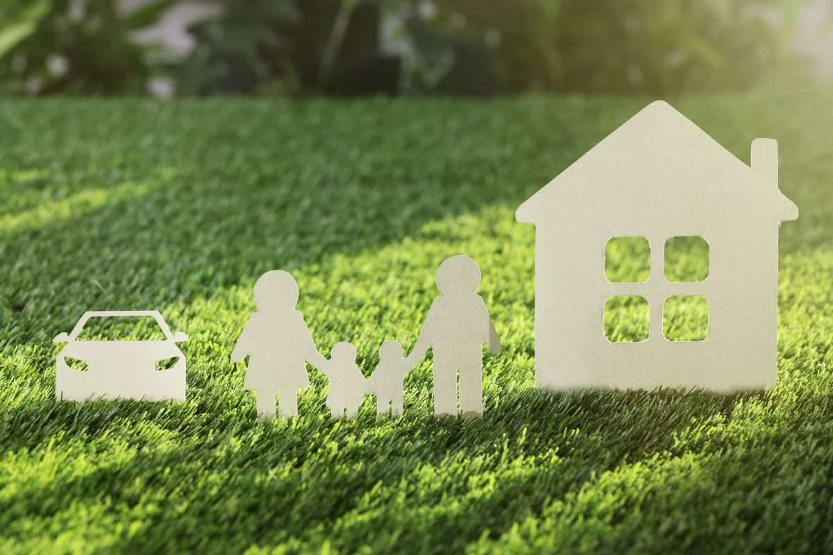 a white paper cut out of a car, a family and a house on a grass background