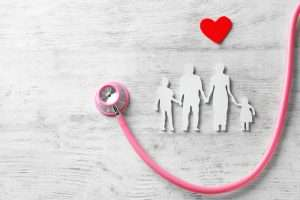 Outline of a family with two children, a pink stethoscope and a small red heart about them
