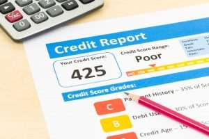 Photo of a credit report with a poor credit score, a pencil and calculator
