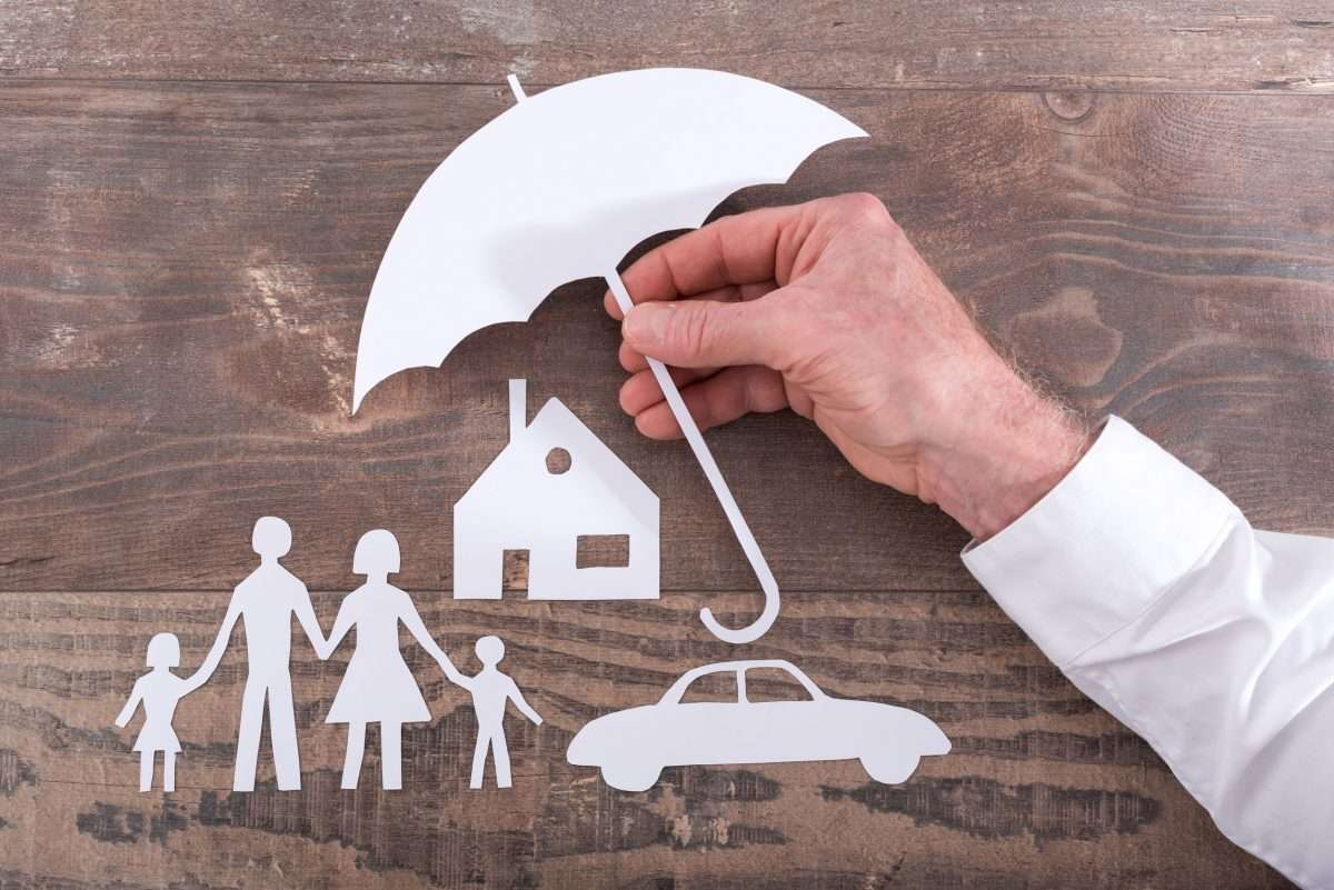 white paper cut out template of a family of stick people with a car and house, covered by a large umbrella being held up by a hand