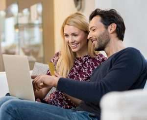 a young couple smiling and looking at properties on a laptop